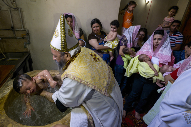 Priest baptizes a child at Coptic Orthodox Church of Virigin Mary in Cairo suburb